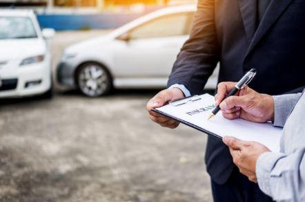 Automobiliste qui signe un contrat d'assurance voiture